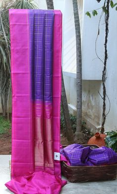 ALLURING PURPLE WITH The gold checked body combines beautifully with the starkly contrasted pink BORDER AND PALLU.