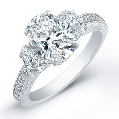 The oval diamond three-stone ring, from Norman Silverman, showcases a 2.10-carat center diamond, oval-cut diamond side stones (0.61 CTW), and an engraved platinum setting.