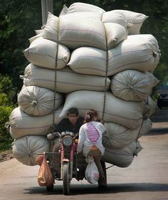 A man and a woman sit on a motor tricycle carrying bags of goods in Nanjing…
