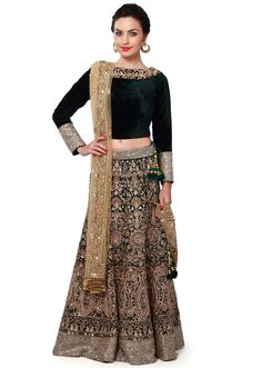 Dark green lehenga featuring in velvet. Its heavily embellished in zardosi and stone embroidery. Blouse is in velvet with neckline and cuff enhanced in stone embroidery. Matched with beige net dupatta. Slight variation in color is possible. 95% of our customers believe that the product is as shown on the website.