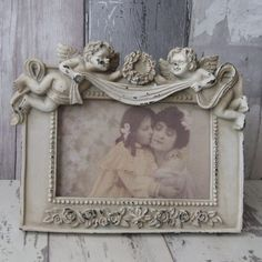 The Victorian Angel Rectangular Shaped Photo Frame has two little cupids sitting together on the top. This pretty resin photo frame is finished with a shabby chic cream distressed paint effect.