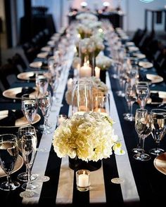 Black and white striped table runner with candles and bowls of full roses in this wedding venue styling
