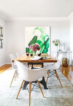 Modern dining room with light gray walls, large art, a simple wooden table, and simple white chairs