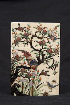 Good quality mid-nineteenth century Japanese ivory and shibayana card case, finely carved with a jardiniere displaying flowers and cherry blossom, beside a pair of scissors and a teapot, the reverse side decorated with exotic birds, flowers and a peach tree, 11cm high x 7.5cm wide
