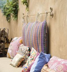Enhance your seating area with a backrest. Use a small curtain rod with decorative finials to re-create the look of this eclectic patio seating area. Just be sure to measure the hanging height of your rod with someone seated there — you don't want it so low that it will be bumped into. Finish by sewing fabric ties to a rectangular cushion and hang it from the rod.