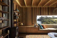 Ubicada en la cima de una montañosa topografía de la costa neozelandesa, esta casa de vacaciones se divide en dos volúmenes para adaptarse el terreno