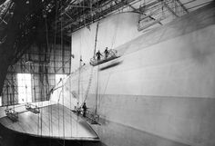 Finishing touches are applied to the A/S Hindenburg in the huge German construction hangar at Friedrichshafen. Workmen, dwarfed in comparison with the ship's huge tail surfaces, are chemically treating the fabric covering the huge hull.