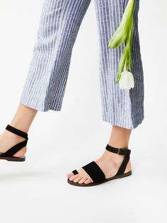 Torrence Flat Sandal   Essential flat sandal featuring a suede design with over-the-foot closures. Adjustable strap wraps effortlessly around the ankle.