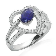 A deep blue oval shaped prong set sapphire gemstone sits in the center of a swirling heart design filled with sparkling diamonds. The diamonds total 64 and have G/H color and SI1/SI2 clarity. All of the diamonds and the gemstone are set in this 18k white gold band.Different ring sizes may be available. Please inquire for details. $960.00