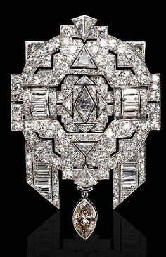 A COLORED AND NEAR COLORLESS DIAMOND BROOCH   The openwork pavé-set diamond plaque centering upon a navette-shaped diamond, enhanced by baguette and triangular-cut diamonds, suspending a detachable brown marquise diamond, mounted in platinum and 18K white gold, with French assay marks and maker's mark