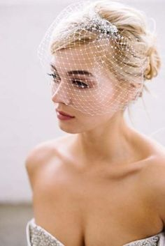 messy updo with a beaded birdcage veil
