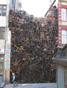 Doris Salcedo, Space is the Place, 8th Istanbul Biennial 2003. 1,550 wooden chairs stacked between two buildings.