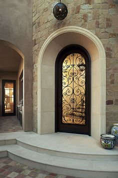 An arched glass door suggests sophisticated elegance. Mediterranean Front Doors, Mediterranean Home Decor, Arched Front Door, Door Molding, Wrought Iron Doors, Spanish Style Homes, Front Door Design, Entrance Doors, Architecture