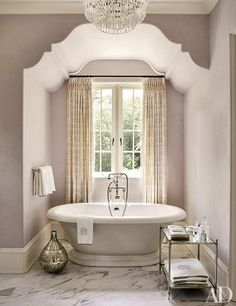Inside an Atlanta home designed by Suzanne Kasler Interiors and William T. Baker & Assoc., the master bath is painted in Benjamin Moore's Violet Pearl and features Waterworks tub fittings.