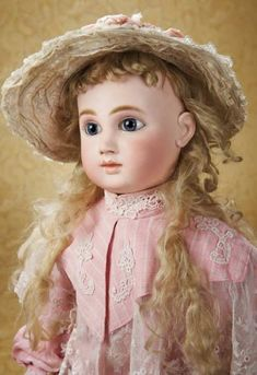 "Very Rare and Beautiful French Bisque Bebe,1885 Series G,by Jules Steiner. 28"" (71 cm.) Bisque socket head with very full elongated cheeks,large blue glass paperweight inset eyes,dark eyeliner,painted lashes with dot highlights,mauve-blushed eye shadow,accented eye corners,shaded nostrils,closed mouth with defined space between the shaded and outlined lips,pierced ears,blonde mohair elongated wig over cork pate,French composition fully-jointed body."