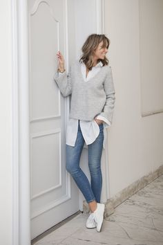 White shirt, gray sweater, jeans and white shoes
