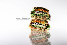 The ultimate veggie sandwich, filled with: lettuce, tomatoes, red onions, sprouts, avocado, red cabbage, and carrots.