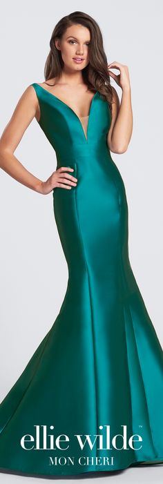 V-neck bow detail prom dress. Sleeveless Mikado trumpet gown with deep curved V-neckline, low V-back finished with a dramatic Obi bow and slight train.