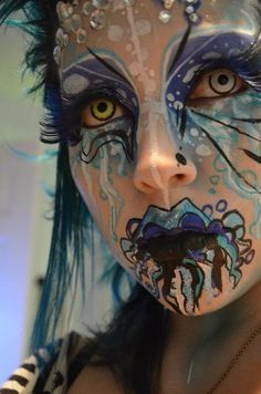 Artistic and colorful water themed fantasy makeup with rhinestone accents, titled 'Flooded'.