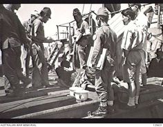 PORT MELBOURNE, VIC. 1946-02-21. SICK JAPANESE INTERNEES BEING CARRIED ABOARD THE KOEI (KOYEI) MARU BY MEDICAL ORDERLIES. THE SHIP, A FORMER MINELAYER STILL CREWED BY JAPANESE NAVAL PERSONNEL, ...