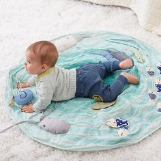 Our washable Activity Floor Mat features appliquéd and embroidered details, textured materials, rattles and squeaker toys to stimulate baby's curiosity