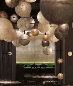 """The custom multi-orb chandeliers hanging in the Pump Room space are made of earth tone 6"""" to 24"""" diameter fiberglass orbs joined with metal framing, Chicago Public Hotel"""