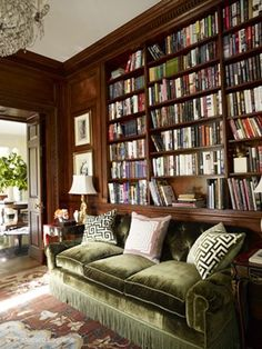 Library with dark wood and a plush, green velvet couch - Miles Redd