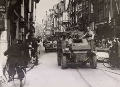 May 7, 1945. The reconnaissance unit of the British 49th (West Riding) Infantry Division also known as Polar Bears enters the center of Amsterdam. On the vehicle (right) Tonny van Renterghem, resistance fighter and founder of the illegal photographer group De Ondergedoken Camera. Photo Beeldbank WO2 - NIOD #amsterdam #worldwar2