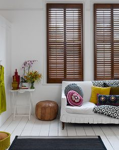 Love the wooden shutters and white walls.