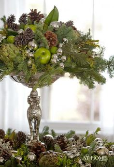 Christmas buffet centerpiece. Evergreens, pinecones, apples, artichokes, limes, and silver ornaments.