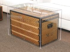Clear acrylic/Lucite tables featuring Louis Vuitton trunks