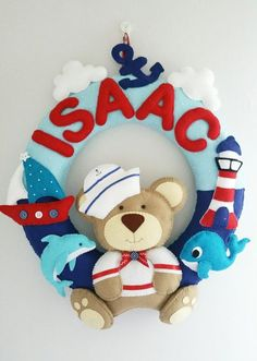 Nautical themed personalised felt name wreath with a cute Teddy bear sailor would look great in a nursery or in a boys bedroom, or as baby shower gift. Looking for a personalised gift? This beautiful personalised felt name wreath with sailor teddy bear is perfect for a little ones bedroom. Garlands/wreaths are hand cut from wool blend felt and hand stitched using cotton embroidery thread. SIZE: Approx 40cm (16 inches) diameter. Colours can be adjusted to customers requirements to match ...