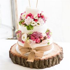 Marks and Spencer wedding cake with fresh flowers wired into poly blocks. Hessian ribbon and hand made mini bunting. On a wooden log cake plate. Fern and field weddings, Farnell Farm, Kent