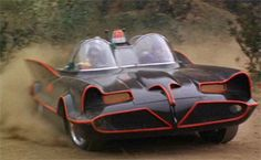 The 60's TV series classic shot of the Batmobile with Batman & Robin tearing out of the Batcave.