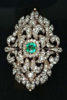 A mid Victorian emerald and diamond brooch/necklace centre, circa 1840. Set to the centre with a step-cut emerald within a cushion-cut diamond cluster surround, to a navette-shaped border composed of cushion and old brilliant-cut diamond entwined foliate motifs, detachable brooch fitting, length 5.9cm. #Victorian #brooch