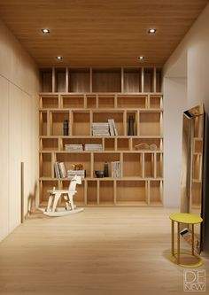 Floor-to-ceiling bookshelves fill the far wall of the library space, otherwise minimally furnished with a charming wood rocking horse by Dutch designer Bo Reudler and a yellow Elios side table by Antonio Citterio.