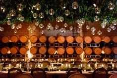 Tables were decorated with low arrangements of greenery and pillar candles, and glass globes filled with tea lights were suspended above in the barrel room. #LightDecor Photography: Elisabeth Millay Photography. Read More: http://www.insideweddings.com/weddings/romantic-neutral-hued-wedding-at-a-paso-robles-california-vineyard/585/