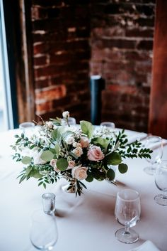 Silver mercury glass compote bowl arrangement with lots of greenery, blush roses, ivory roses, spray roses and heather. Industrial wedding venues, low centerpieces, romantic wedding centerpieces. Florals: Wildflowers LLC, Photography: Eden Ingle, Venue: One Cannery, Nashville, TN
