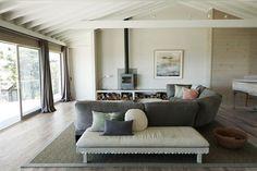 Una cabaña remodelada para disfrutar en familia  Sobre la alfombra de fibra, un sofá Eternal Dreamer define el living. En el estante con tapa de mármol, lámpara de mesa Scorpion (todo de Ochre) y estufa (Chesney´s)