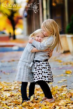 Two little girls hugging on a fall day.