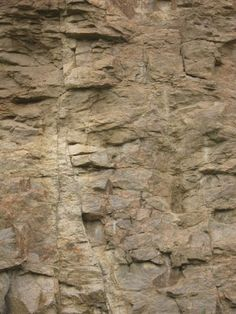 Rock cliff texture in light brown tones with very jagged, cracked surface.