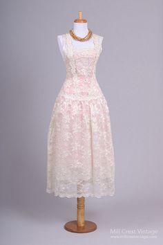 Conçu dans les années 70, cette robe de mariée vintage incroyable, faite dans un filet transparent avec chatoyante blanc et écru poly mélange floral dentelle et strass, dispose de tout le grand style d'une robe des années 1920 de gaine taille haute goutte. Si vous envisagez de faire un mariage sur le thème «Great Gatsby», c'est la robe pour vous. Cette robe n'est pas doublée, mais nous avons jumelé avec une doublure slip satin pêche (non incluse) pour montrer comment il pourrait être…