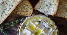 Creamy Camembert is sliced crosshatch style, stuffed with garlic and thyme and baked.