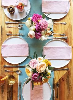 Spring brunch table with pastel napkins and bright flowers.