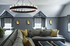 Gorgeous gray family room boasts to gray washed desks positioned behind a gray pit sectional topped with gray and yellow pillows lit by a Ralph Lauren Roark Modular Ring Chandelier.