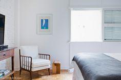 Quarto clean e bem iluminado tem parede de tijolinho branco e poltrona vintage.