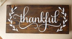 """Wooden Sign with Handwritten """"Thankful"""" in White Paint"""