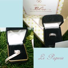 """I came across this most creative invitation from Le Paperie and had to share it.  Looking for a unique wedding invite and willing to paid a little extra for postage?  I got one for you.  I absolutely love this idea.  It's a ring box that when opened you will see a paper ring with a """"stone"""" on it.  Unwrap the ring and read the wedding invitation.  Very unique and cool!  What do you think?"""