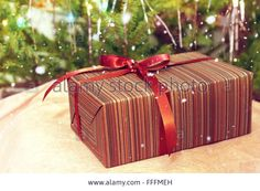 Download this stock image: New Christmas gift on the background of fir dressed up and falling snow. - FFFMEH from Alamy's library of millions of high resolution stock photos, illustrations and vectors.