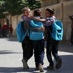 Dei bambini portano in spalla gli zainetti distribuiti dall'UNICEF ad Hazeh, nell'area orientale di Ghouta, in Siria, nell'area circostante la capitale Damasco